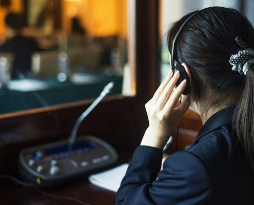 simultaneous interpreter in booth 495x400 - ترجمه و یا تفسیر همزمان به چه معنی است ؟